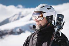B?rtiger m?nnlicher Skifahrer des Nahaufnahme-Portr?ts gealtert gegen Hintergrund des Schnee-mit einer Kappe bedeckten Kaukasus S lizenzfreie stockfotografie