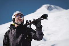 B?rtiger m?nnlicher Skifahrer des Portr?ts gealtert gegen Hintergrund des Schnee-mit einer Kappe bedeckten Kaukasus Ein tragender lizenzfreie stockfotos