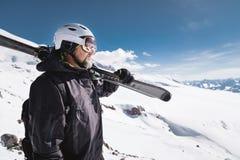 B?rtiger m?nnlicher Skifahrer des Portr?ts gealtert gegen Hintergrund des Schnee-mit einer Kappe bedeckten Kaukasus Ein tragender stockfoto