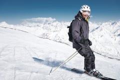 B?rtiger m?nnlicher Skifahrer in einem Sturzhelm und Bremsen einer Sturmhaube mit Schneepulver auf Skis vor dem hintergrund Schne lizenzfreie stockfotos