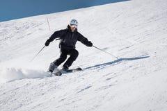 B?rtiger m?nnlicher Skifahrer in einem Sturzhelm und in einer Sturmhaube f?hrt auf eine Steigung mit Geschwindigkeit und Bremsen  lizenzfreie stockfotografie