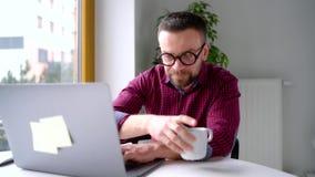 Bärtiger Mann in den Gläsern, die zu Hause Büro sitzen und an einem Laptop arbeiten stock footage