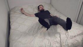 Bärtiger Mann, der auf Bett in der Zeitlupe fällt stock video