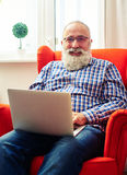 Bärtiger Mann, der auf dem Stuhl mit Laptop stillsteht Lizenzfreie Stockbilder