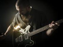 Bärtiger Mann, der Bass-Gitarre spielt Stockbild