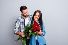 Bärtiger Mann, der Blumenstrauß von roten Rosen seinem Bezaubern, Zufall darstellt Stockbilder