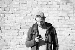 Bärtiger Mann in der braunen Hoodiejacke mit Sporttasche, Telefon Lizenzfreie Stockfotografie