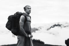 Bärtiger Mann, der in den Bergen, über den Wolken steht Stockfoto