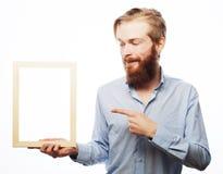 Bärtiger Mann, der einen Bilderrahmen hält Stockbilder