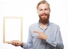 Bärtiger Mann, der einen Bilderrahmen hält Lizenzfreies Stockfoto
