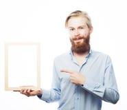 Bärtiger Mann, der einen Bilderrahmen hält Lizenzfreie Stockfotos