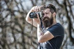 Bärtiger Mann, der Foto am sonnigen Tag macht Schwarzer Hintergrund Mann mit dem langen Bart beschäftigt mit Schießenfotos Mann m stockbild