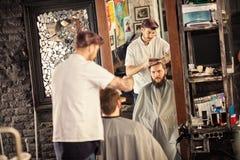 Bärtiger Mann, der Haarschnitt durch Friseur erhält Lizenzfreies Stockbild