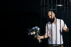 Bärtiger Mann, der heraus einen Blumenstrauß mit Blumen hält Der grobe Mann im Käfig über schwarzem Hintergrund Lizenzfreie Stockfotografie