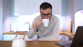 Bärtiger Mann, der in der Küche frühstückt und einen Laptop verwendet stock footage