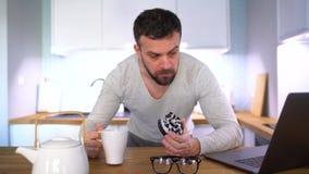 Bärtiger Mann, der in der Küche frühstückt und einen Laptop verwendet stock video