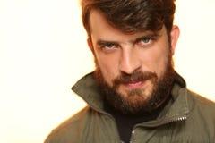 Bärtiger Mann, der kakifarbige Jacke mit interessantem Blick trägt abschluß Herauf weiß Lizenzfreie Stockfotografie