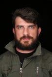 Bärtiger Mann in der kakifarbigen Jacke, die die Kamera untersucht abschluß Herauf schwarzes Stockfotografie