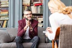 Bärtiger Mann, der nach erfolgreichem Gespräch mit privatem Therapeuten lächelt lizenzfreies stockbild