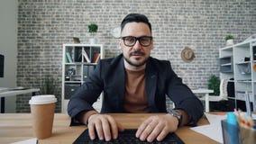 Bärtiger Mann, der online unter Verwendung des Computers betrachtet die Kamera gestikuliert in Büro spricht stock video
