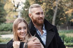 Bärtiger Mann der Rothaarigen, der nette blonde Frau umarmt Lizenzfreie Stockbilder