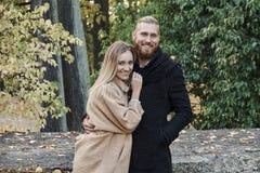 Bärtiger Mann der Rothaarigen, der nette blonde Frau umarmt Stockfoto