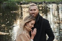 Bärtiger Mann der Rothaarigen, der nette blonde Frau umarmt Stockfotografie