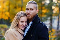 Bärtiger Mann der Rothaarigen umarmt die nette blonde Frau Lizenzfreie Stockfotos