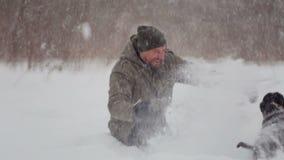 Bärtiger Mann, der sein Haustier in den Schneefällen geht stock video