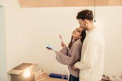 Bärtiger Mann, der seine Frau wählt Farben kommt und umarmt stockfoto