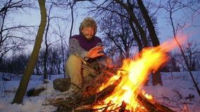 Bärtiger Mann, der seine Hände durch das Feuer im Winter wärmt Touristisches Mannabendlagerfeuer stock footage