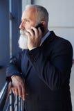 Bärtiger Mann, der am Telefon beim Fenster heraus schauen spricht Stockbild