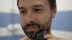 Bärtiger Mann, der Trimmer rasiert stock footage