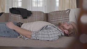 B?rtiger Mann in der zuf?lligen Kleidung, die auf dem Sofa liegt Unscharfe Flasche im Vordergrund Es gibt Verwirrung in der Wohnu stock footage