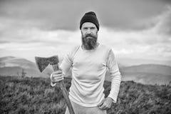 Bärtiger Mann des Holzfällers mit Axtstand auf Berglandschaft Lizenzfreie Stockfotografie