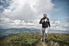Bärtiger Mann des Sportlers laufen gelassen auf Berglandschaft Lizenzfreie Stockfotos