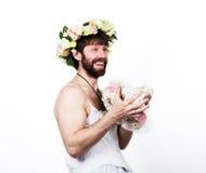 Bärtiger Mann in einem Frau ` s Hochzeitskleid auf ihrem nackten Körper, Holding eine Blume Auf seinem Kopf ein Kranz von Blumen  Lizenzfreies Stockfoto