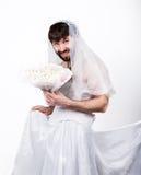 Bärtiger Mann in einem Frau ` s Hochzeitskleid auf ihrem nackten Körper, Holding eine Blume Auf seinem Kopf ein Kranz von Blumen  Stockbild