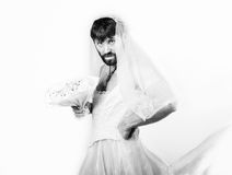 Bärtiger Mann in einem Frau ` s Hochzeitskleid auf ihrem nackten Körper, Holding eine Blume Auf seinem Kopf ein Kranz von Blumen  Stockbilder
