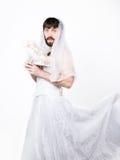 Bärtiger Mann in einem Frau ` s Hochzeitskleid auf ihrem nackten Körper, Holding eine Blume Auf seinem Kopf ein Kranz von Blumen  Stockfoto