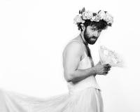 Bärtiger Mann in einem Frau ` s Hochzeitskleid auf ihrem nackten Körper, Holding eine Blume Auf seinem Kopf ein Kranz von Blumen  Stockfotos