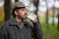 Bärtiger Mann holt eine Flasche zu seinem Mund im Herbstwald Stockbilder