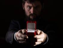 Bärtiger Mann im Anzug gibt einen Ring im roten Kasten und drückt verschiedene Gefühle auf dunklem Hintergrund aus Stockfotografie