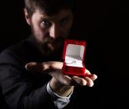 Bärtiger Mann im Anzug gibt einen Ring im roten Kasten und drückt verschiedene Gefühle auf dunklem Hintergrund aus Stockfoto