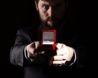Bärtiger Mann im Anzug gibt einen Ring im roten Kasten und drückt verschiedene Gefühle auf dunklem Hintergrund aus Lizenzfreie Stockfotos
