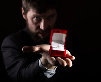 Bärtiger Mann im Anzug gibt einen Ring im roten Kasten und drückt verschiedene Gefühle auf dunklem Hintergrund aus Stockbild