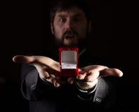 Bärtiger Mann im Anzug gibt einen Ring im roten Kasten und drückt verschiedene Gefühle auf dunklem Hintergrund aus Lizenzfreies Stockfoto