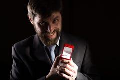 Bärtiger Mann im Anzug gibt einen Ring im roten Kasten und drückt verschiedene Gefühle auf dunklem Hintergrund aus Stockfotos
