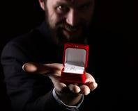 Bärtiger Mann im Anzug gibt einen Ring im roten Kasten und drückt verschiedene Gefühle auf dunklem Hintergrund aus Lizenzfreies Stockbild