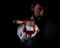 Bärtiger Mann im Anzug gibt einen Ring im roten Kasten und drückt verschiedene Gefühle auf dunklem Hintergrund aus Stockbilder